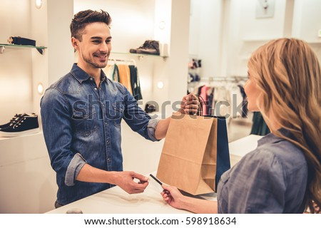 Handsome shop assistant is smiling while giving purchases and credit card to beautiful client #598918634