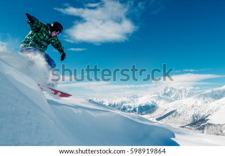 snowboarder is riding with snowboard from powder snow hill or mountain very fast #598919864