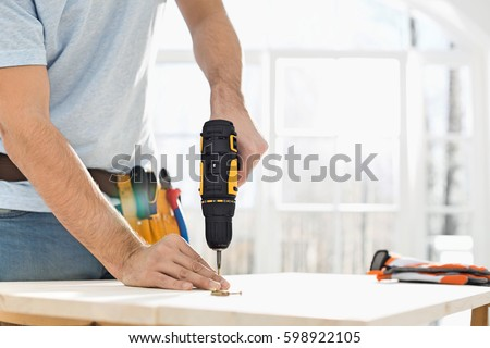 Midsection of man drilling nail on table #598922105