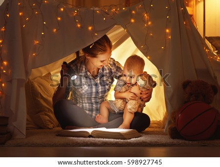 reading and family games in children's tent. mother and child daughter with  book and flashlight before going to bed #598927745