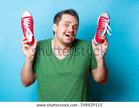 handsome young man holding red gumshoes on the wonderful blue background #598929155