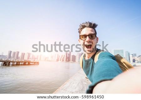 Happy tourist caucasian man having fun taking a selfie at New York city