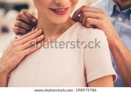 Cropped image of beautiful couple smiling while choosing jewelry in the shopping mall Royalty-Free Stock Photo #598979786