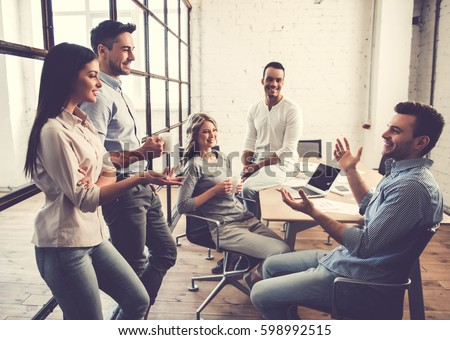 Beautiful business people are using gadgets, talking and smiling during the conference in office #598992515