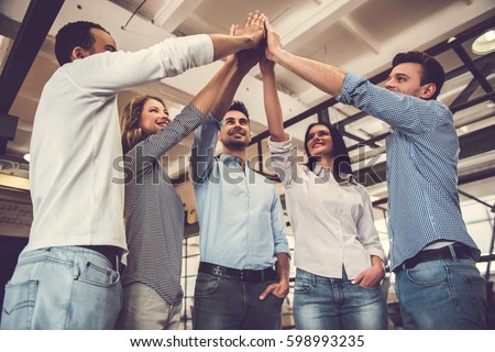 Successful business team is giving high five and smiling while standing in office #598993235