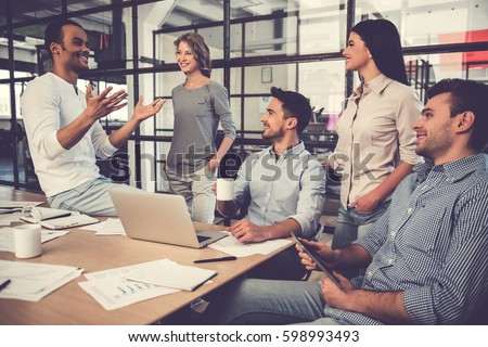 Beautiful business people are using gadgets, talking and smiling during the conference in office Royalty-Free Stock Photo #598993493