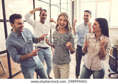 Successful business team is raising hands in fists and smiling while standing in office #598994465