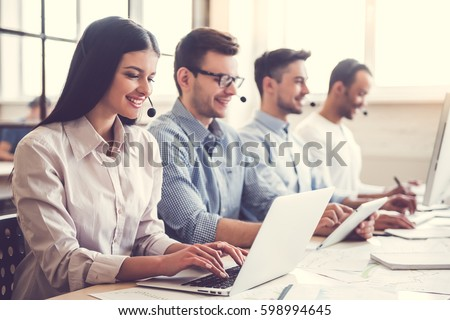 Beautiful business people in headsets are using computers and smiling while working in office Royalty-Free Stock Photo #598994645