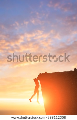 silhouette of businesswoman with dangerous problem in cliffs #599112308