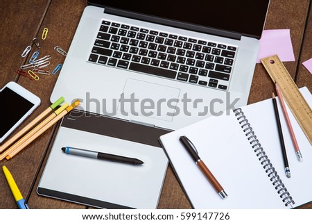 Workspace for office and design laptop smartphone pen tablet and other stationary on wood desk