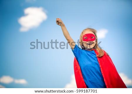 Funny little girl plays super hero over blue sky background. Superhero concept. #599187701