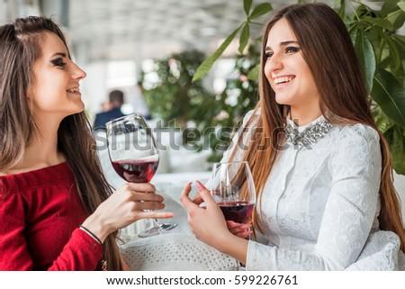Two female friends drinking wine in restaurant #599226761