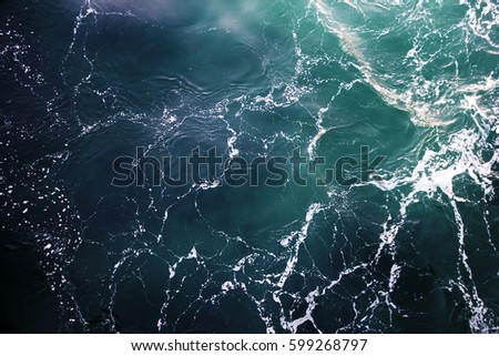 Blue-green waves on the surface of the ocean. Top view of the water.  Royalty-Free Stock Photo #599268797