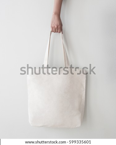 Blank canvas tote bag, design mockup with hand. Handmade shopping bags. Royalty-Free Stock Photo #599335601
