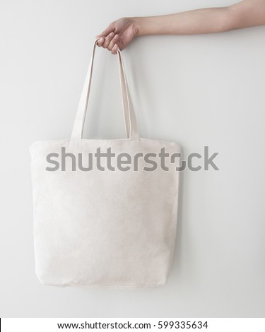 Blank canvas tote bag, design mockup with hand. Handmade shopping bags. #599335634
