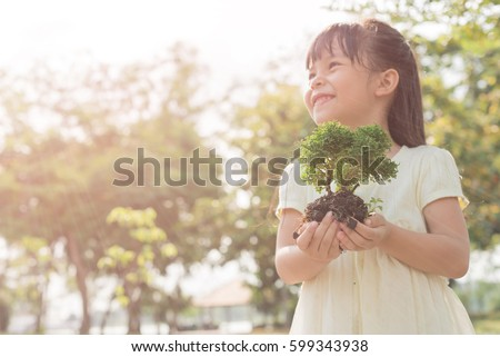 Kid holding young plant in hands against spring green background. Ecology concept Royalty-Free Stock Photo #599343938