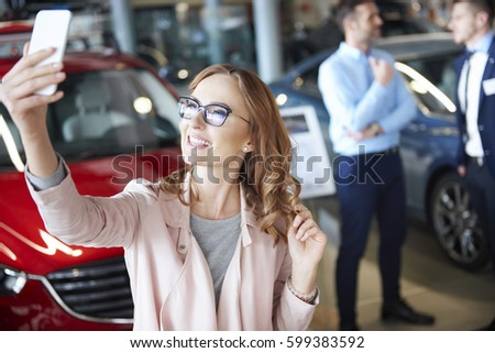 Young woman taking picture in the car dealership