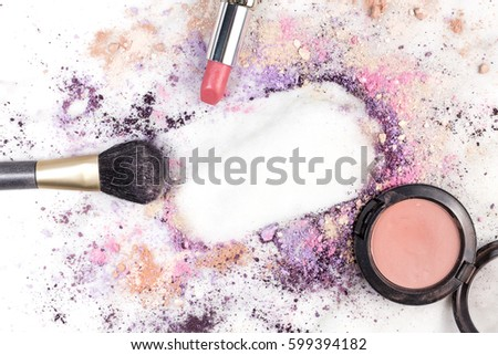 Makeup brush, lipstick, and powder on a white marble background, with traces of cosmetics forming a frame. A horizontal template for a makeup artist's business card or flyer design, with copy space
