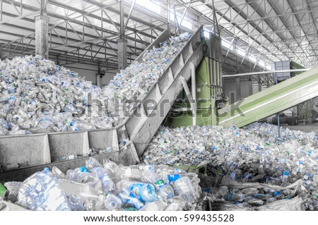 closeup escalator with a pile of plastic bottles at the factory for processing and recycling. PET recycling plant Royalty-Free Stock Photo #599435528