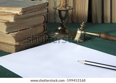 On the table are: old books, a candle in a bronze candlestick, a white sheet of paper and a simple pencil #599453168