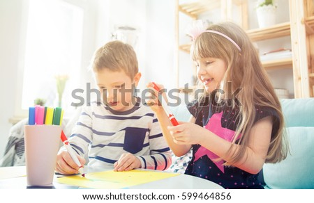 Brother and sister drawing with colorful pencils together at home #599464856