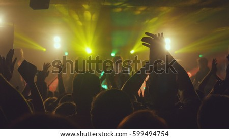 Fans waving their hands at rock concert in night club on beautiful golden lights #599494754