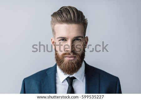 Stylish handsome bearded businessman looking at camera isolated on grey Royalty-Free Stock Photo #599535227
