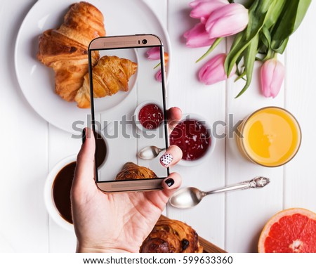 Woman's hand taking photo of delicious breakfast with croissants with smart phone.