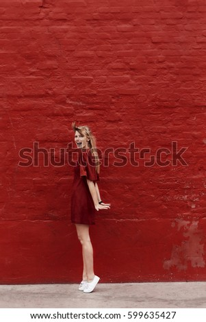 Beautiful blond woman in red against red wall, portrait