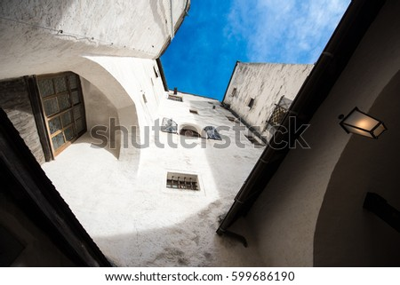 White walls and windows of ancient building and blue sky #599686190