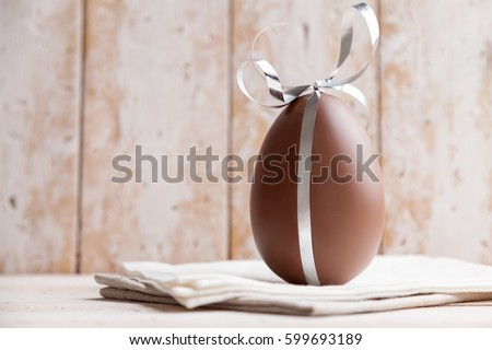 Delicious seasonal chocolate Easter egg with a ribbon Royalty-Free Stock Photo #599693189