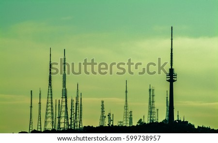 Silhouettes of telecommunication mast TV antennas with blue sky background #599738957