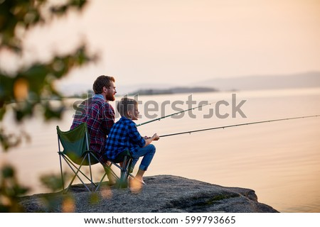 Side view portrait of father and son sitting together on rocks fishing with rods in calm lake waters with landscape of setting sun, both wearing checkered shirts, shot from behind tree Royalty-Free Stock Photo #599793665