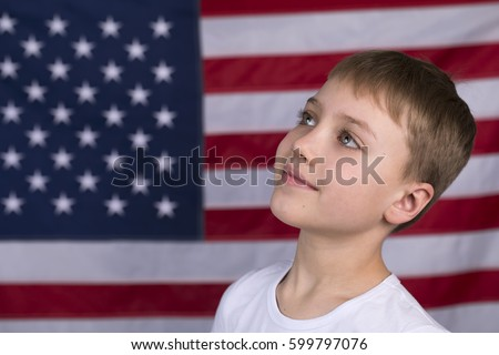 Portrait of Caucasian little boy with American flag in background #599797076