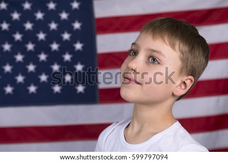 Portrait of Caucasian little boy with American flag in background #599797094