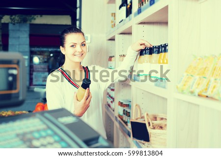 Young female customer examining various juices in grocery shop #599813804