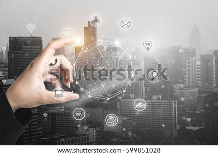 Businessman holding smart phone with wireless communication network icon and cityscape background.E-commerce smart connection business. internet of things. #599851028