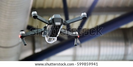 Flying drone with camera. Quadcopter flying indoor. Professional small drone with video camera hanging in the air. Concept: an innovative high-tech #599859941