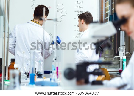 Portrait of young scientists carrying out an experiment in a laboratory. #599864939