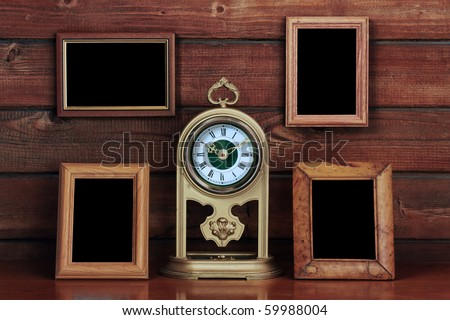 old photo frames and antique clock on wooden table