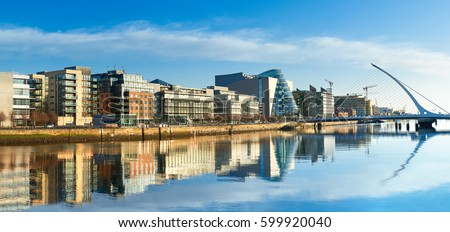 Modern buildings and offices on Liffey river in Dublin on a bright sunny day, bridge on the right is a famous Harp bridge.  #599920040
