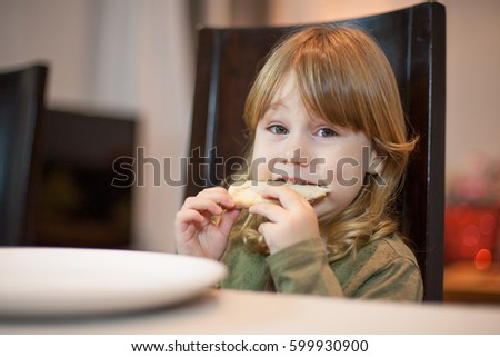 Three years old blonde hungry child biting pizza piece in her hands, sitting in dark brown chair, in table with grey tablecloth at home, looking at camera #599930900