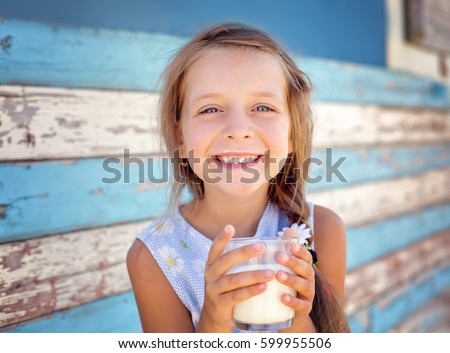 Cute little girl is drinking milk outdoors. #599955506