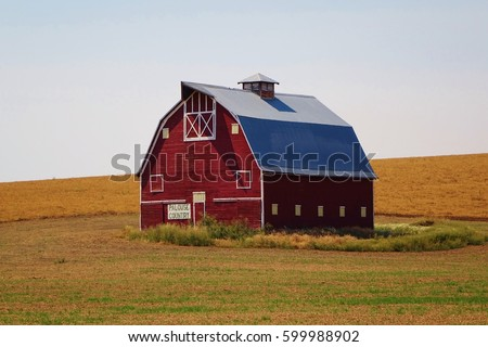Red barn on the Palouse in eastern Washington state. The barn is on the rolling hills of a wheat farm along the Palouse Scenic Byway, Highway 195, near Uniontown. Taken on a nice blue sky summer day.