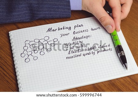Man shows presentation of business concepts network marketing and business structures diagram, advantages in notepad on the table #599996744