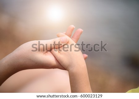 hands of mother and baby closeup #600023129