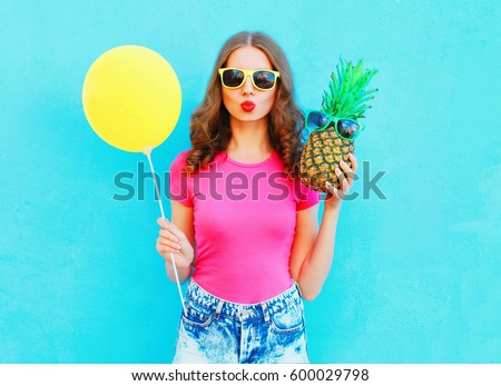 Fashion pretty woman with yellow air balloon and pineapple wearing a pink t-shirt over colorful blue background #600029798