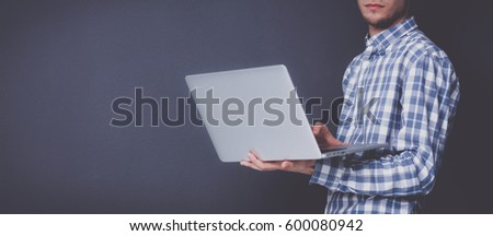 Portrait of confident young man with laptop standing over gray background #600080942