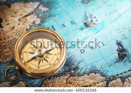 Old compass on vintage map. Adventure stories background. Retro style Royalty-Free Stock Photo #600126266