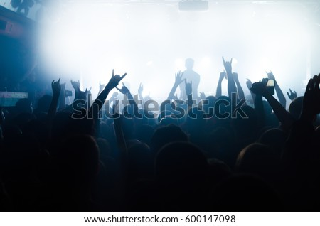 silhouettes of people at a rock festival concert in front of the scene in bright light #600147098